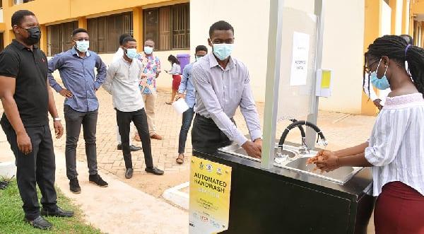 Three Engineering students build automatic hand washing station. 1